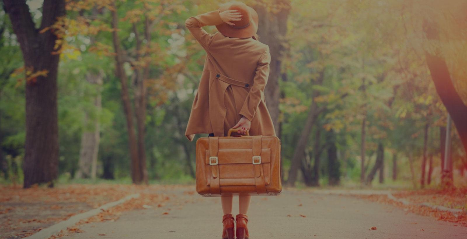 Жена в есенни дрехи държаща куфар в парк