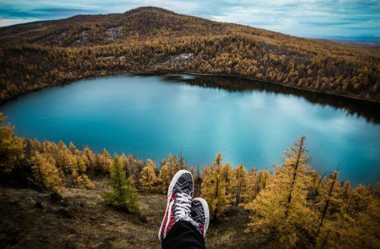 Турист с кръстосани крака почиващ на хълм гледащ към езеро