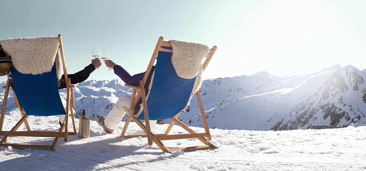 Двойка седнала на сгъваеми столове наслаждаваща се на чаша бяло вино в Австрия